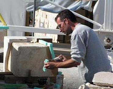 Acropolis restoration worker shapes marble block